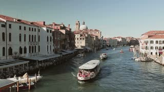 VENICE, ITALY - JULY 28 2015: Boats with tourists pass on the Grand Canal, as seen from the Ponte degli Scalzi bridge.