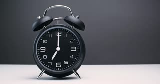 An old-fashioned alarm clock with bells ringing at 7 o'clock in the morning. Studio shot with copy space.