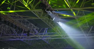 Stage lights and projectors in different colors lighting an event hall ceiling.