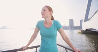 Woman relaxing on a city bridge after a workout.