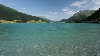 Wide and low angle static footage of lake Lago di Resia, also known as Reschensee by summer with blue sky and nearly transparent water.