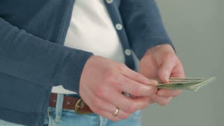 Woman counts cash (US dollars), puts it in her pocket and leaves the frame.