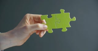 Woman holding two puzzle pieces joined together. Chroma key compositing possible.