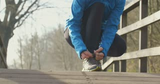 Woman jogging in a park - tying shoelaces.