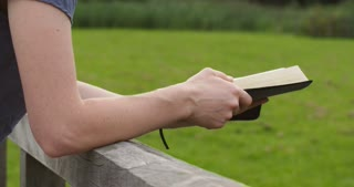 Woman reading the Bible, closes it and walks away.