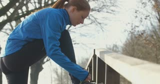 Woman running in a park - tying shoelaces.