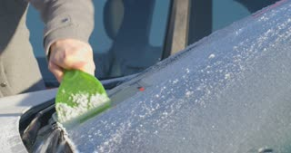 Woman scraping ice off the windshield of a parked car.