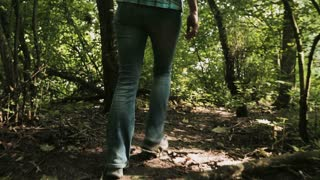 Woman walks in a forest and stops before dense vegetation.