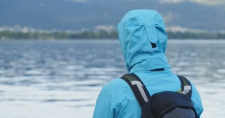 Woman with a rain jacket and backpack looks at a lake and walks out of frame.