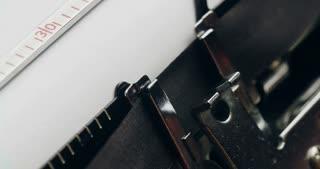 Writer types THE END on a typewriter. Extreme closeup shot.
