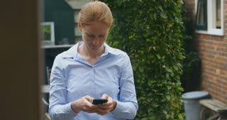 Young redhead businesswoman texting from a home or office garden.
