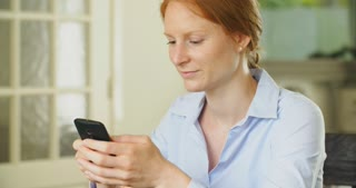 Young redhead businesswoman using a mobile phone at home.