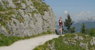Young woman hikes alone on a mountain trail by summer.