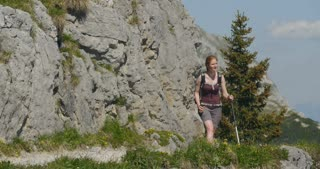 Young woman hikes alone on a mountain trail on a sunny summer day.