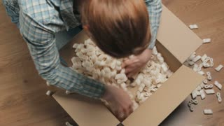 Young woman looking for a product in a carton box filled with packaging insulation foam. Static footage, top view.
