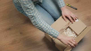 Young woman looking for a product in a carton box filled with packaging insulation foam.