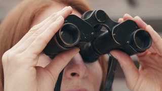 Young woman looking through vintage binoculars.