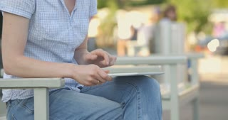 Young woman using a tablet on her lap in a city center. Locked down medium shot.