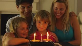 Boy blowing out candles on birthday cake.