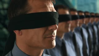 Businessman in a line-up removing his blindfold.