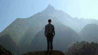 Businessman raising his arms while looking mountain.