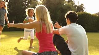 Children running to parents in garden.