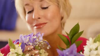 Close up dolly shot of woman smelling flower scent.