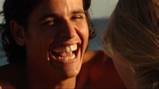 close-up man's face laughing, couple on beach