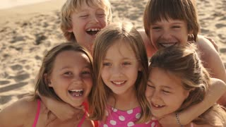Close up of five children on beach facing camera and laughing.