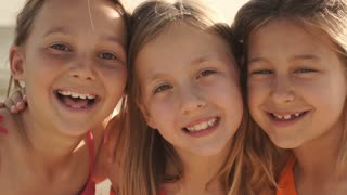 Close up of three girls playing on beach laughing to camera.
