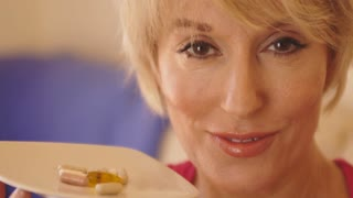 Close up of woman taking vitamin pill.