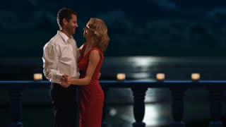 Couple dancing on a balcony at night.