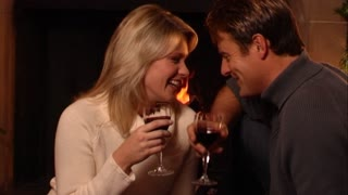Couple drinking wine in front of fire at Christmas.