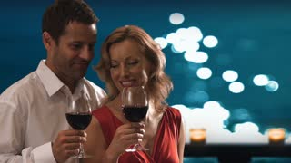 Couple drinking wine together in moonlight.