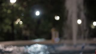 Couple embracing beside a water fountain at night.