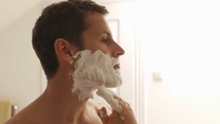 Couple embracing while man is shaving.