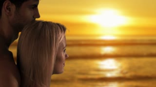 Couple gazing at sun setting over the ocean.
