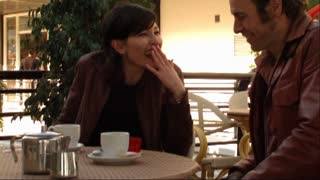 Couple in town, having coffee, man gives present to woman