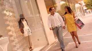 Couple in walking in street with shopping bags