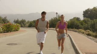 Couple jogging on road in countryside.