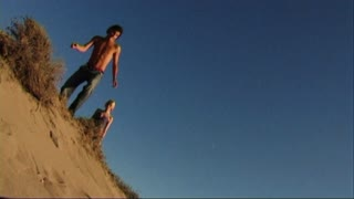 Couple jumping in sand dune on beach