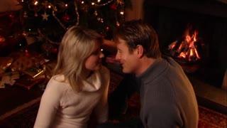 Couple kissing under mistletoe at Christmas.