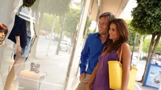 Couple looking in shop window with shopping bags