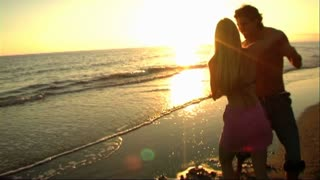 couple on beach at sunset embracing and dancing in sea