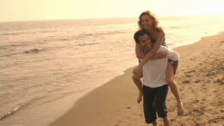 Couple on beach, man carrying woman.