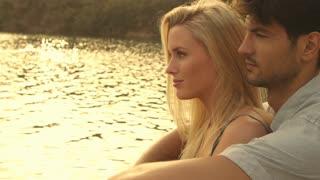 Couple sitting together on dock beside lake.