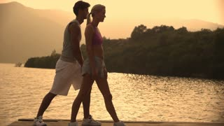 Couple stretching on dock beside water.