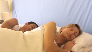 Couple waking up in bed and cuddling.