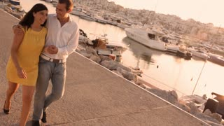 Couple walking by marina in sunset