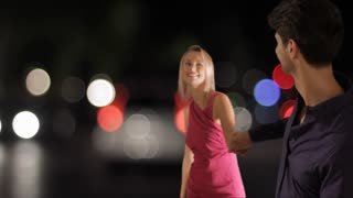 Couple walking on the street in town at night.